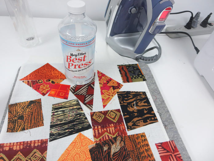 Fabric pieces, and iron and a bottle of Mary Ellen's Best Press sitting on a pressing table. Brother Innov-ís BQ3050 sewing and quilting machine, MuVit Digital Dual Feed Foot, SA195 MuVit Open-Toe Dual Feed Foot, Mary Ellen's Best Press, Banyan Batiks