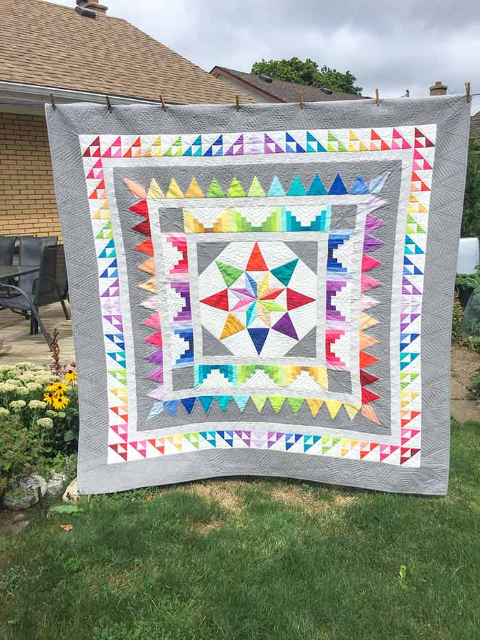 The colorful quilt shown was the inspiration for the machine embroidered quilt label.