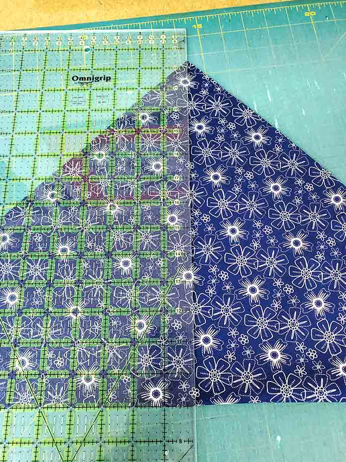 A quilter's ruler placed on a large blue and white triangle of fabric. Spectrum QAL2020 made with the Blue Stitch collection by Riley Blake Designs