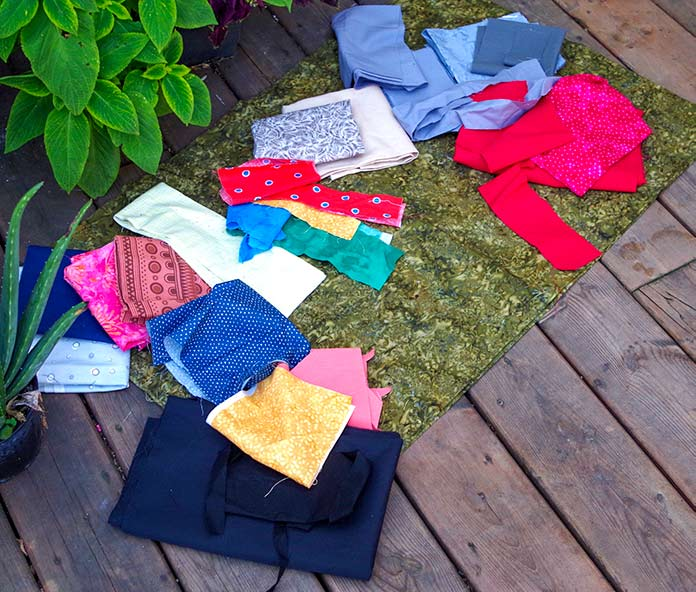 Scraps of fabrics of various colors (oranges, blues, black, pink, grays, reds, beige) are displayed on the green-leaf fabric that will be used as the background for each bird.