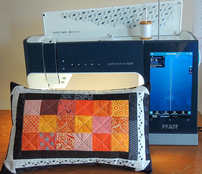 Quilted fall accent pillow with PFAFF performance icon.