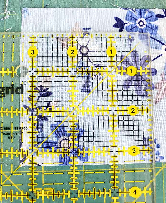 """Cutting a quilt square at 35/16"""" inch using a square ruler. Block 3 with Blue Stitch fabric collection by Riley Blake Designs."""