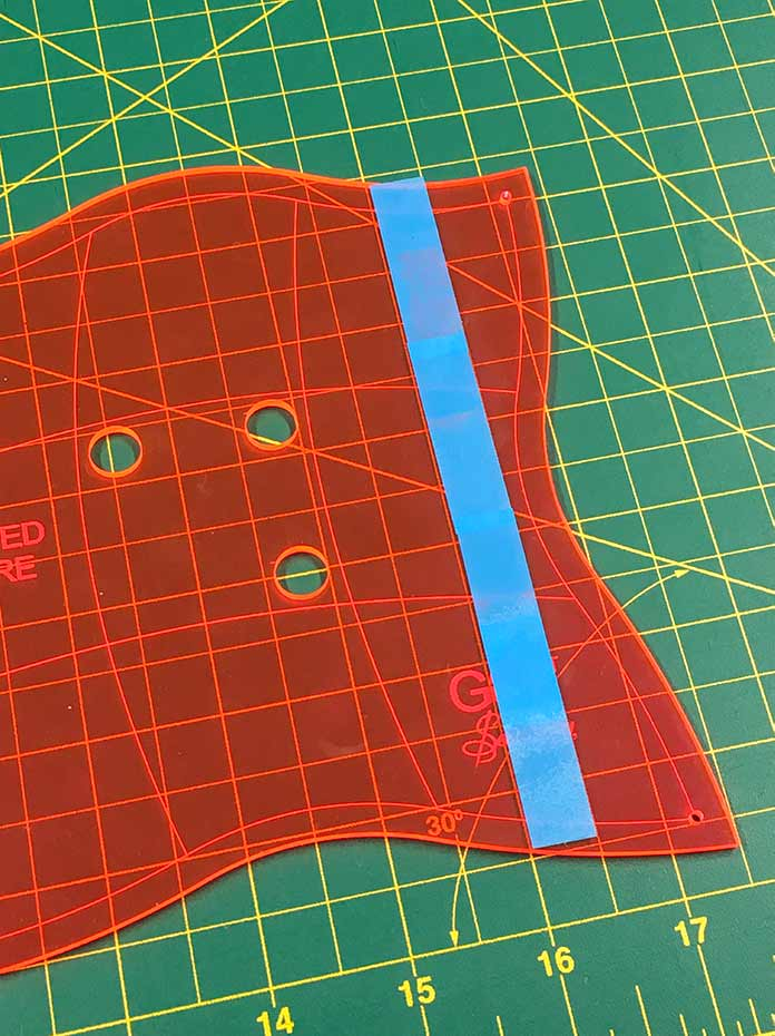 The cutting guide is marked on the curved template using tape or small sticky notes.