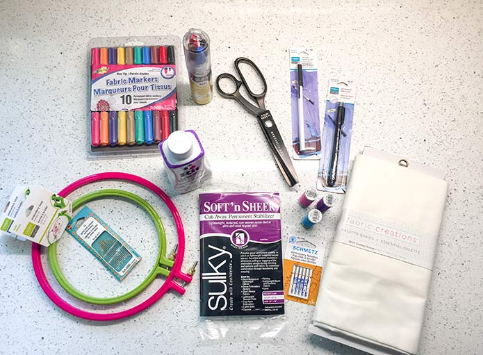 "Supplies needed to make quilt labels like UNIQUE Craft Embroidery Hoops, UNIQUE SEWING Laundry Marking Pen & Permanent Marking Pens, Sulky Soft and Sheer Stabilizer & Transfer Pens, SCHMETZ Machine Embroidery Needles, Heirloom Crewel Embroidery Needles, Fabric Creations Cotton, Fabric Fun Fabric Markers & LDH 9"" Pinking Sheers, RIT Color Stay Liquid Dye Fixative, Gütermann Machine Embroidery Thread & Fabric Creations White Cotton"