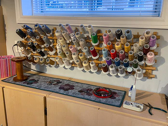 Cones of quilting threads can be stored on large wooden racks that hang on the wall.