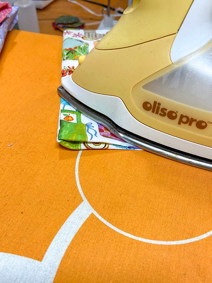 The sewn rectangle shown being pressed by a yellow iron on an orange iron board cover.