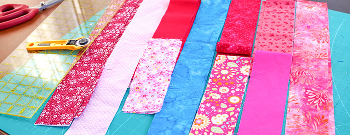 Scissors, cutter and ruler are shown next to several strips of red, pink, blue and flowered red and pink fabric on a cutting mat.