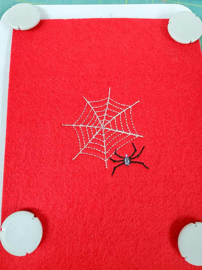 The spider web embroidery design has been stitched stitched out on heavy red felt.