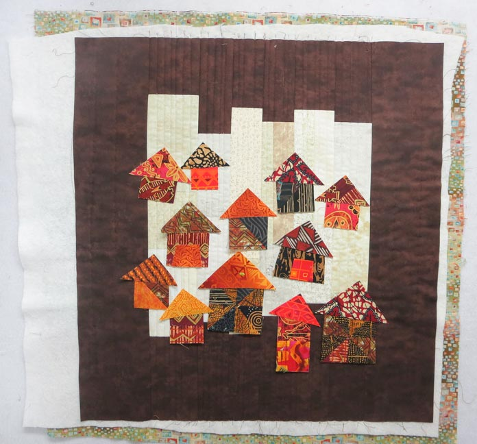 House shapes placed on a quilted background. Brother Innov-ís BQ3050 sewing and quilting machine, MuVit Digital Dual Feed Foot, SA195 MuVit Open-Toe Dual Feed Foot, Mary Ellen's Best Press, Banyan Batiks