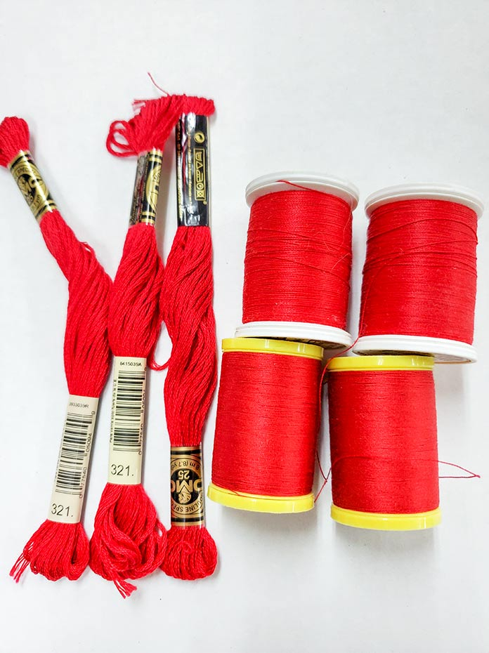 Four spools of red thread and three skeins of red embroidery floss. Husqvarna Viking Brilliance 75Q sewing machine, Husqvarna Viking Topstitch needle, Inspira Tear-A-Way Stabilizer, Singer Steam Craft Plus Steam Iron, Singer Ironing and Crafting Station, Gütermann Threads