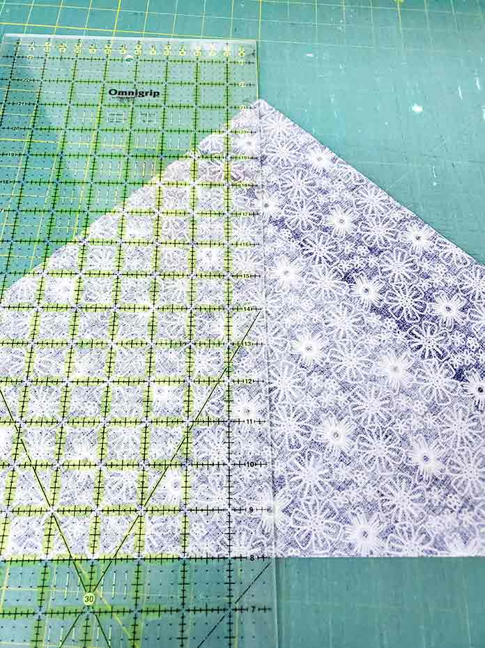 A triangle of blue and white fabric under a quilter's ruler. Spectrum QAL2020 made with the Blue Stitch collection by Riley Blake Designs