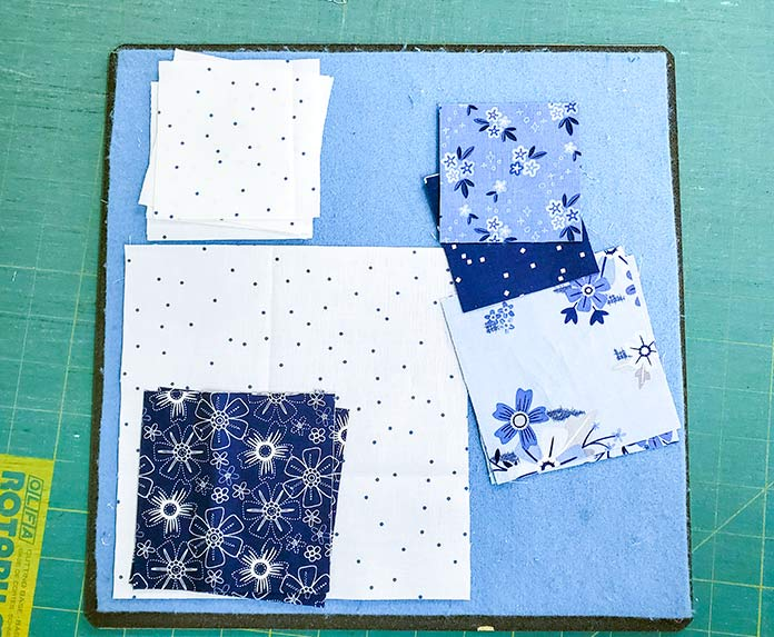 The pieces for the first block using the Blue Stitch fabric collection by Christopher Thompson for Riley Blake Designs is positioned on a small design board
