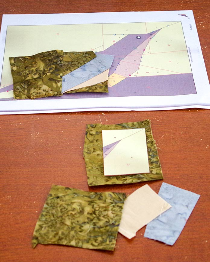 n the top photo, you can see section B of the nuthatch piecing with the green , beige and gray fabric. Section B has been sewn together showing the start of the body and the green background. The bottom photo shows the setup of the green on Section C with the background green and the beige and gray for the next part of the body.