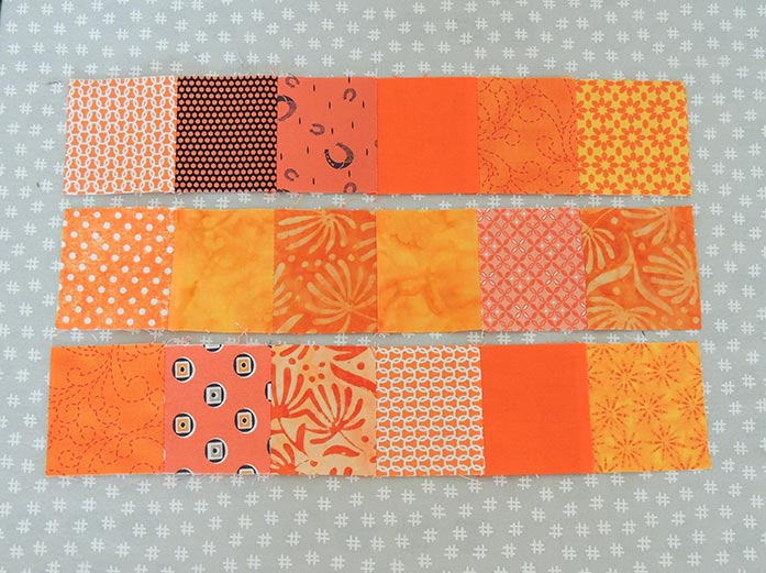 Patchwork Program chain piecing three rows of orange squares on the PFAFF performance icon