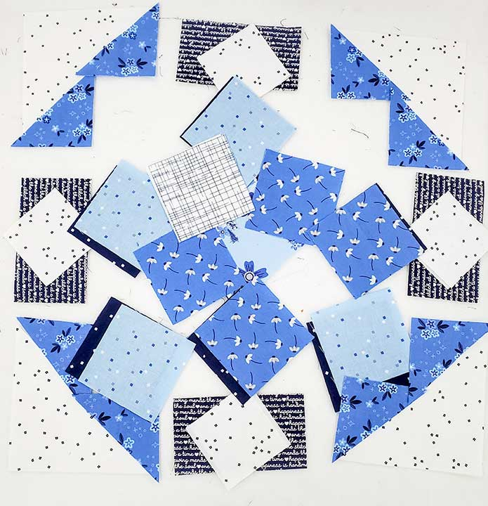 Blue and white fabric squares on a white design board.