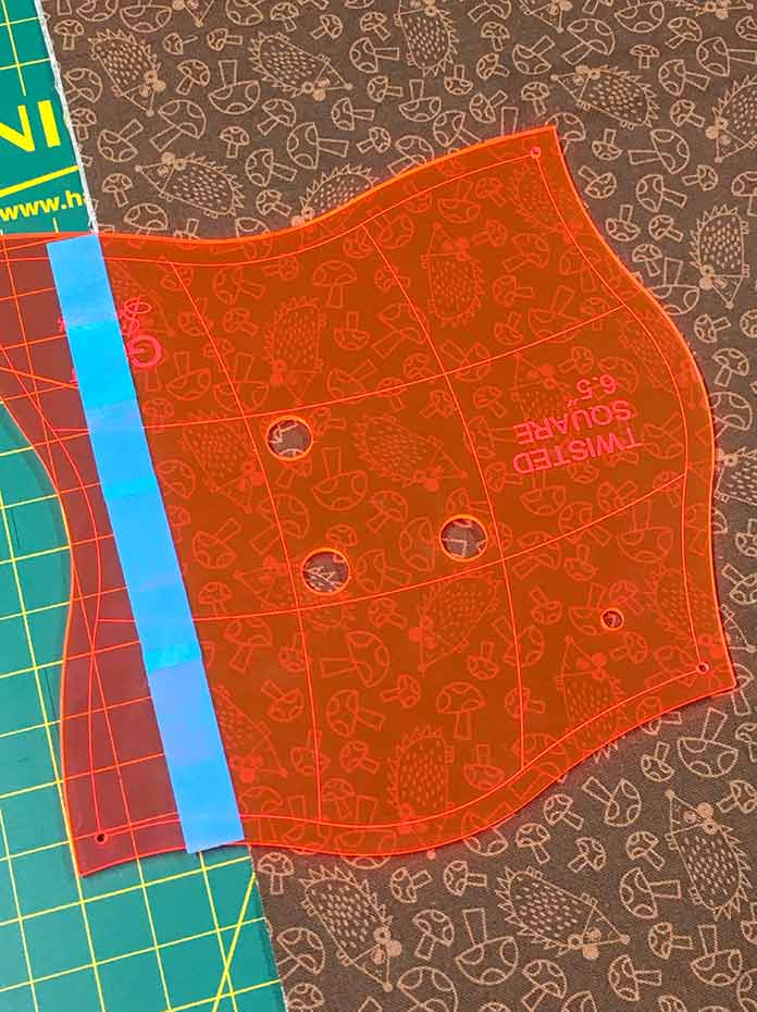 The cutting guide on the Twisted Square Template by Sew Easy is placed along the edge of the folded fabric.