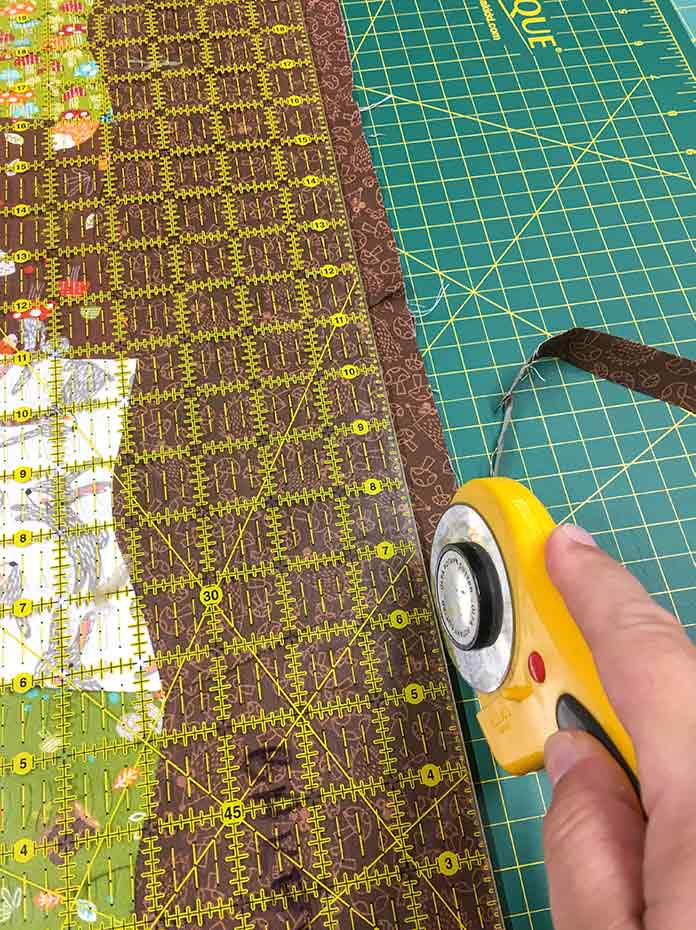 An Olfa rotary cutter, Omnigrid ruler, and UNIQUE cutting mat are used to trim off the excess fabric from the brown border.