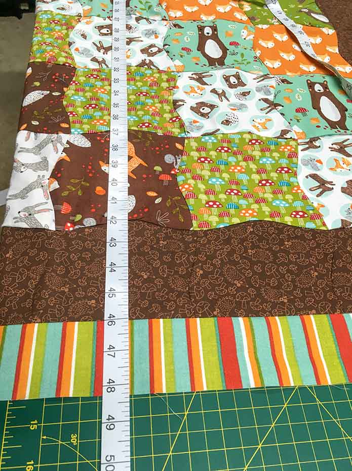 The length of the multicolored quilt is measured through the center of the quilt using a measuring tape.