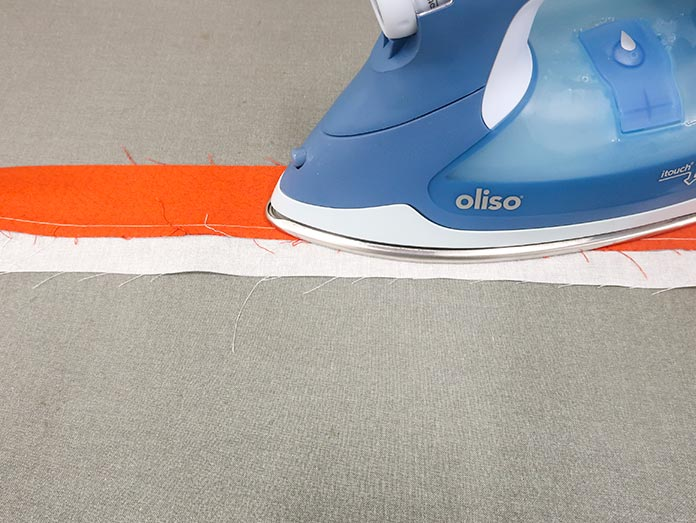 The two fabric strips are being pressed toward the binding fabric.
