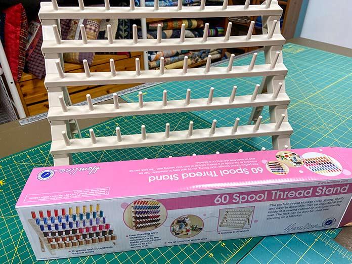 An assembled Hemline 60 Spool Thread Stand and box shown sitting on a green cutting mat.