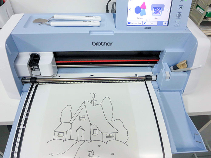 Place drawn design on the scanning mat, Brother ScanNCut SDX225, Brother scanning mat, Brother fabric mat, Brother blue erasable marking pen, Heat n Bond Feather Lite, Brother color pen set