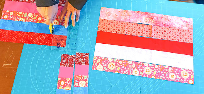 "2½"" ruler cutting strips that will be sewn together to create hearts. Two different combinations of strips are shown in a variety of colors (red, pink, blue) with some showing flowered patterns."