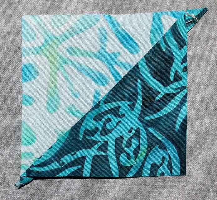 "Press the seams to the darkest fabric and open to make a 2½"" square; a half square triangle"