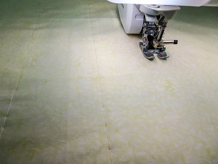 Backing and batting are basted together with a sewing machine. Brother Innov-ís BQ3050 sewing and quilting machine, MuVit Digital Dual Feed Foot, Sugar Crystals collection by Banyan Batiks