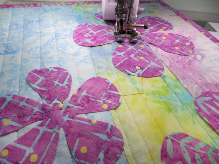 Pink fabric flowers basted into place on a quilted background. Innov-ís BQ3050 sewing and quilting machine, MuVit Digital Dual Feed Foot, Sugar Crystals fabric collection by Banyan Batiks, Brother ScanNCut SDX225 cutting machine, Brother CADBLDQ1 Thin Fabric Auto Blade, Brother CADXMATF12 Fabric Mat