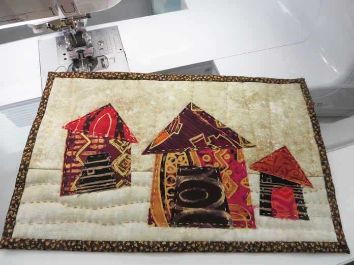 """Hand-stitched raw edge applique house mini quilt. Brother Innov-ís BQ3050 sewing and quilting machine, Mary Ellen's Best Press, Brother SA185 ¼"""" Piecing Foot with Guide, Brother SA125 ¼"""" Quilting Foot, Olfa square ruler, MuVit digital dual feed foot"""