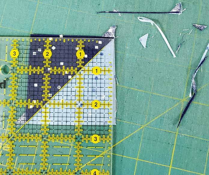 """Trimming a half-square triangle unit to 2½"""". Block 3 with Blue Stitch fabric collection by Riley Blake Designs."""