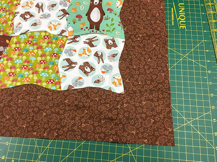 Once trimmed, the brown curved border on the quilt made with the Twisted Square Template from Sew Easy looks amazing.