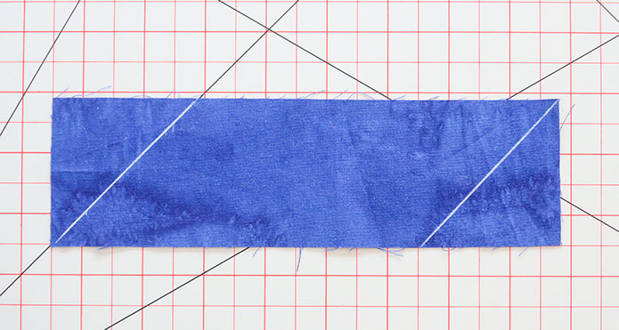 A strip of binding fabric with 45o diagonal lines drawn at each end