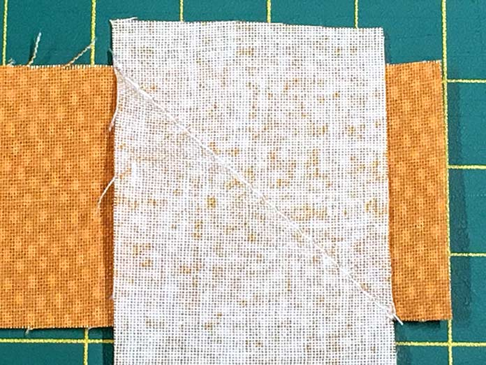 Join the border cut from the orange dot Forest Friends fabric with a mitered join and then press seams open.