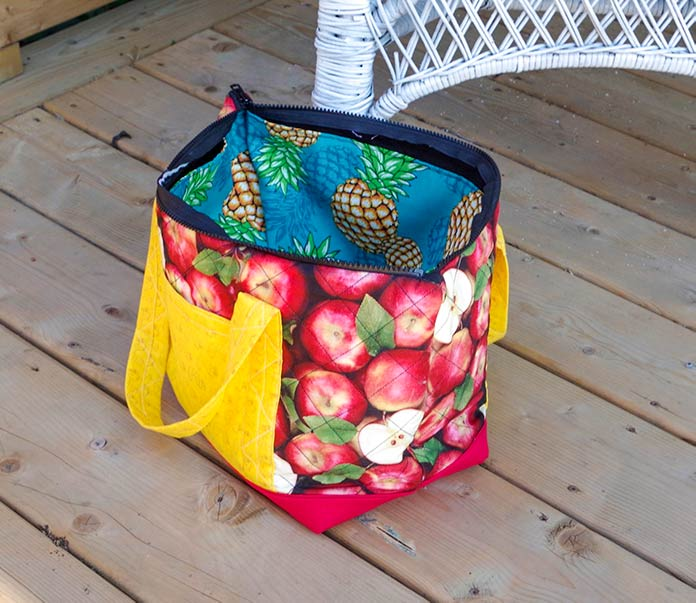 The bag is sitting on the stone path. You can see the apple pattern at the end of the bag and the red bottom of the bag. You can see the strap and pocket on the right side of the bag and a bit of the strap on the left side of the bag. You can see the pineapples on the inner pocket of the bag.