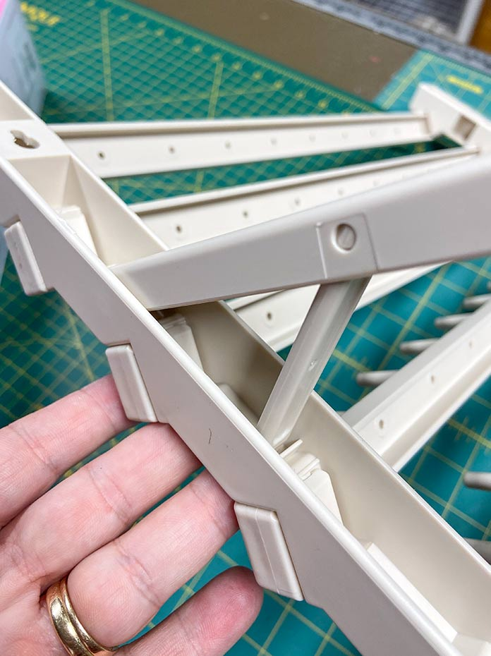 The stabilizer brace on the leg of the Hemline 60 Spool Thread Stand comes down to secure the leg in place so the stand won't fold up by accident.