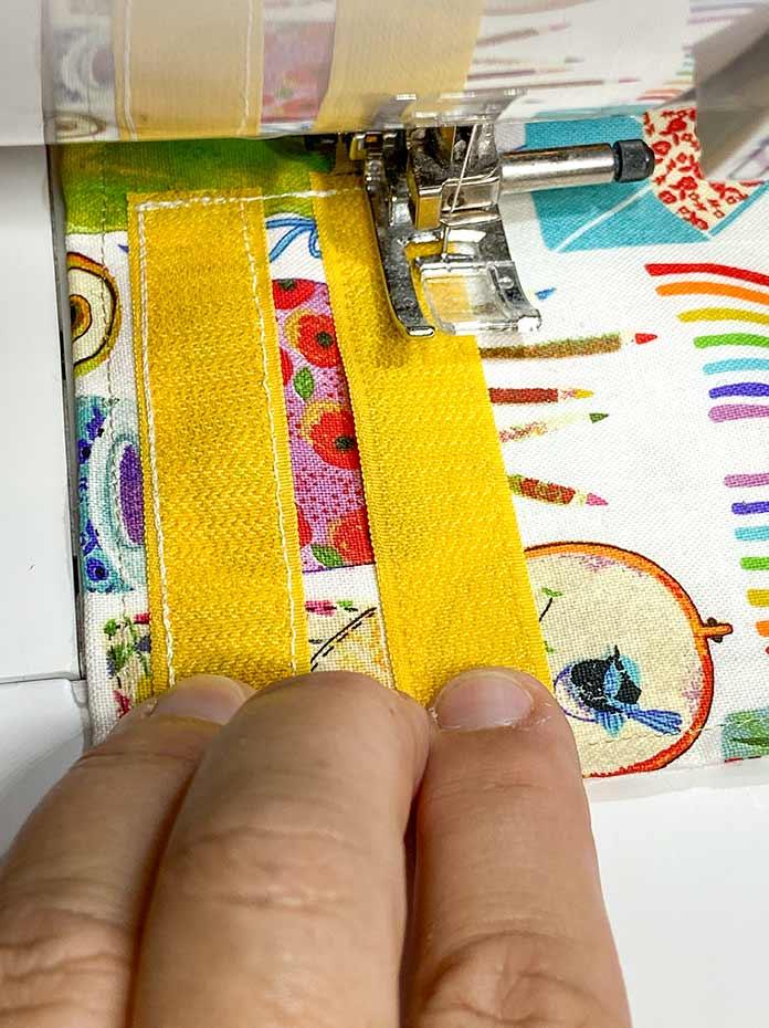 Sew on hook strips of hook and loop tape.