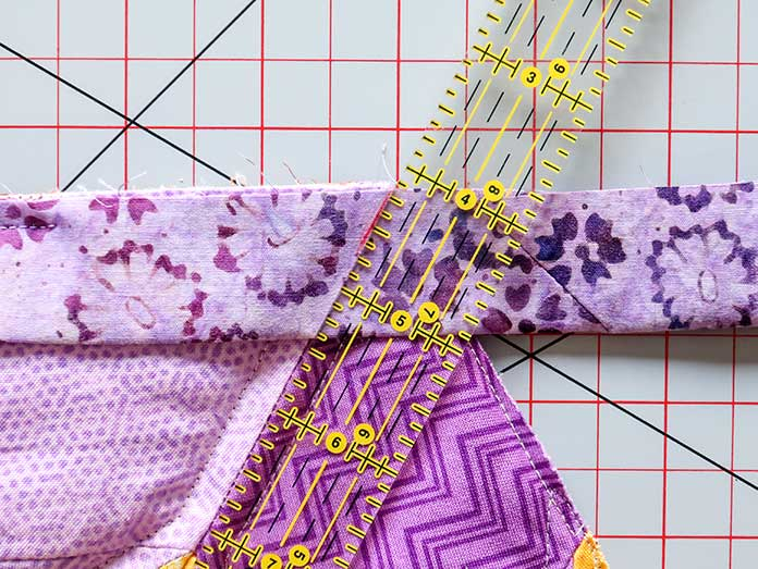 A ruler is lined-up along a seam leading to a quilt's corner edge to determine where to draw the short diagonal line.