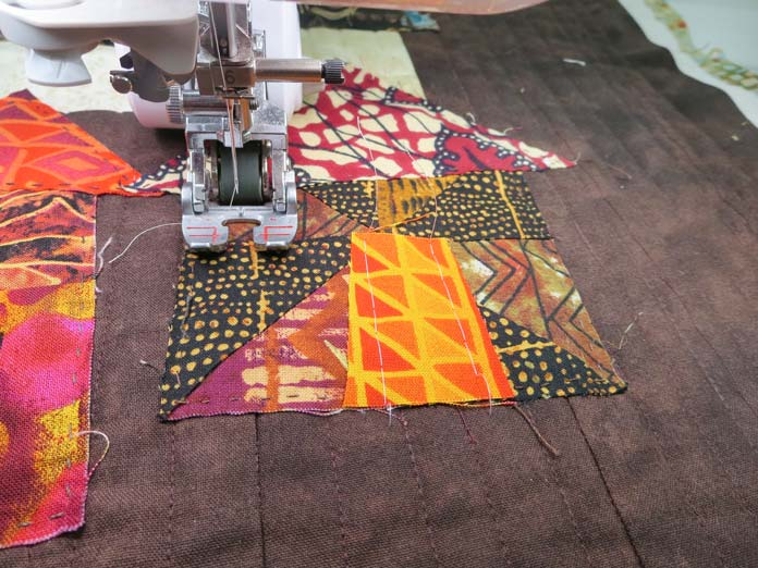 Fabric pieces under the presser foot of a sewing machine. Brother Innov-ís BQ3050 sewing and quilting machine, MuVit Digital Dual Feed Foot, SA195 MuVit Open-Toe Dual Feed Foot, Mary Ellen's Best Press, Banyan Batiks