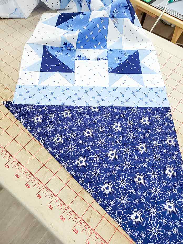 A large blue and white triangle sewn to one side of a blue and white quilt block. Spectrum QAL2020 made with the Blue Stitch collection by Riley Blake Designs