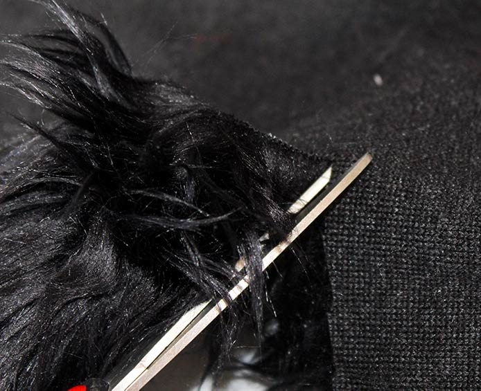 Cutting the Fabric Creations Faux Fur with scissors.