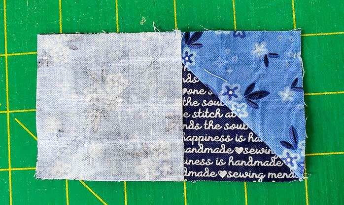 A square of blue fabric sewn to a rectangle of dark blue fabric