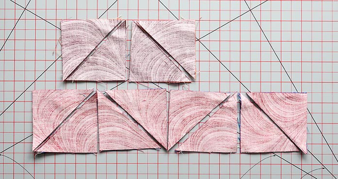 With seams sewn on each side of the diagonal lines, the fabric pieces are then cut along each marked line.