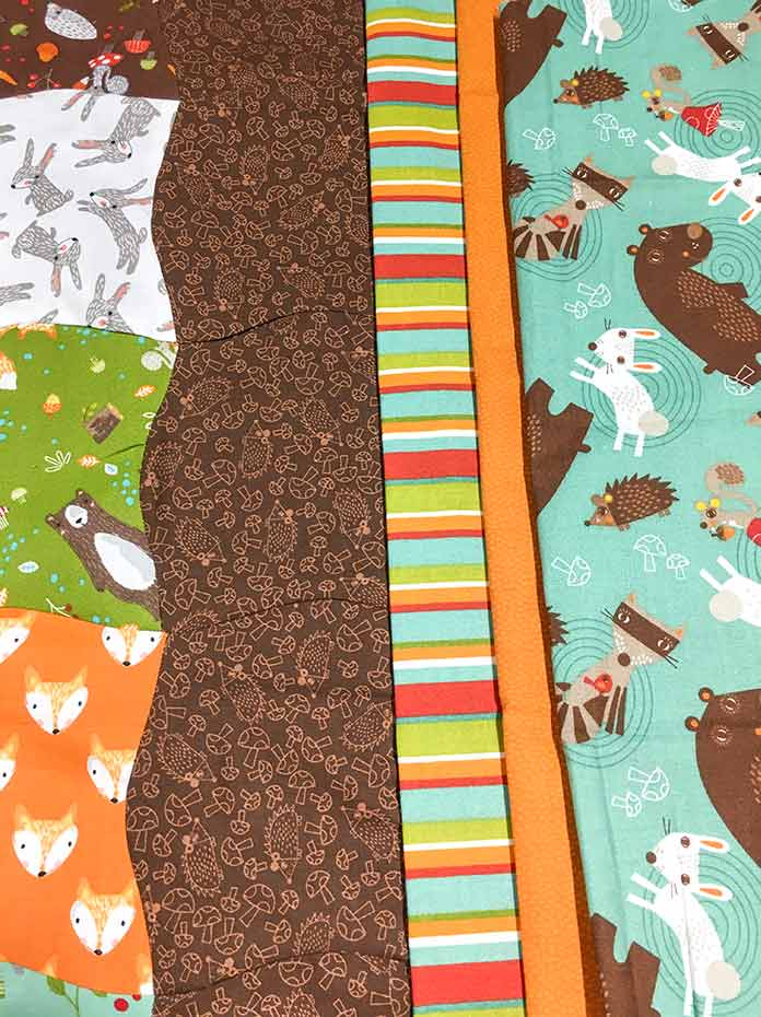 Different borders for your quilt can be previewed by folding fabrics into widths and placing them beside the quilt.