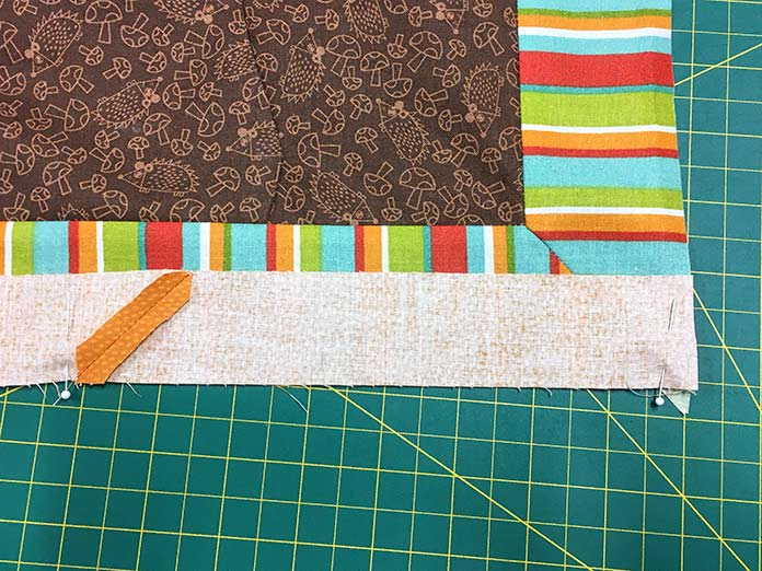 Divide the quilt and the border into 4 even sections and then match up the ends and the points with the pins and pin the two layers together. You now have your border spaced evenly along the side of your quilt.