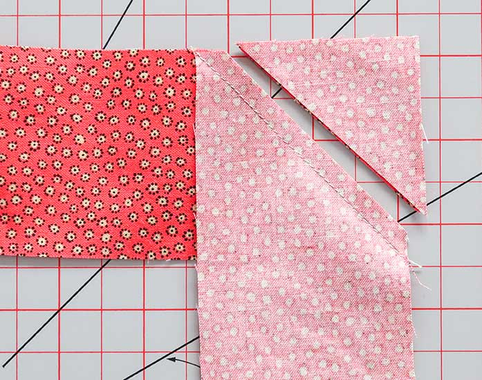 "Two strips of fabric are sewn right sides together along the 45o diagonal line and trimmed ¼"" from the seam"