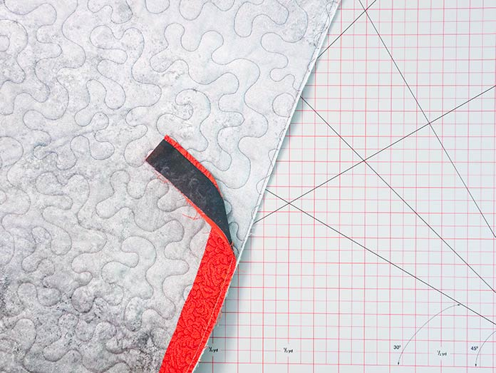 The binding strip is sewn to the quilt with the binding fabric against the quilt back.