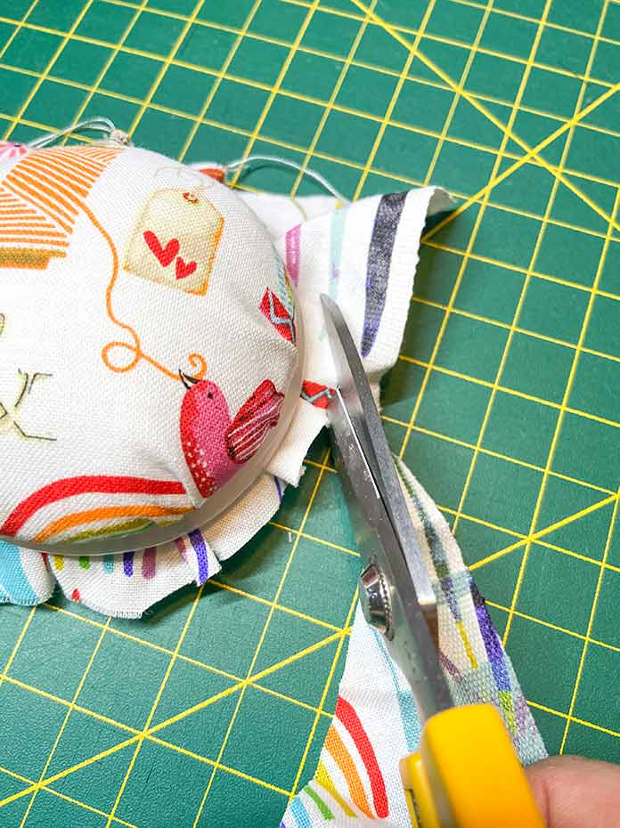 The silicone ring of the Clover Create-a-Pincushion secures the fabric, and excess fabric is trimmed away with scissors.