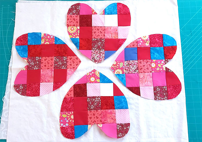 The four different hearts showing the small squares of different colors on them are laid out on the white background.