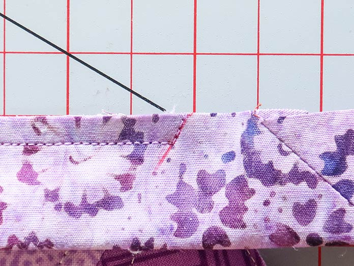 A seam is sewn as usual to the drawn diagonal line, and then turned to continue sewing towards the edge of the quilt.